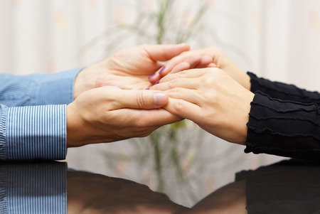 couple holding hands in counseling